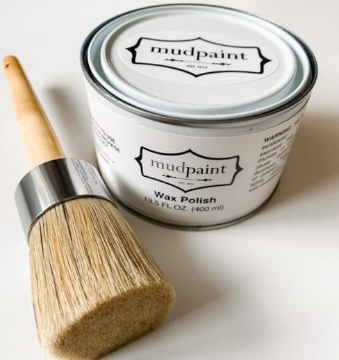 Natural bristle brush lying beside a container of MudPaint finishing wax polish